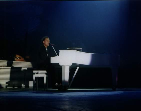 immagine di un pianoforte a coda bianco su di un palco illuminato