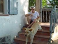 sorridente uomo brizzolato, seduto sugli scalini con il suo cane-guida, in pantaloncini blu e maglietta bianca...io